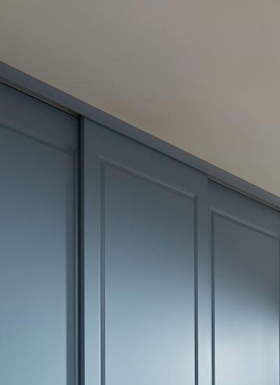 Rahmenlose Holzschiebetür in Denum blau mit farbiger Deckenblende als Schiebetür Zubehör