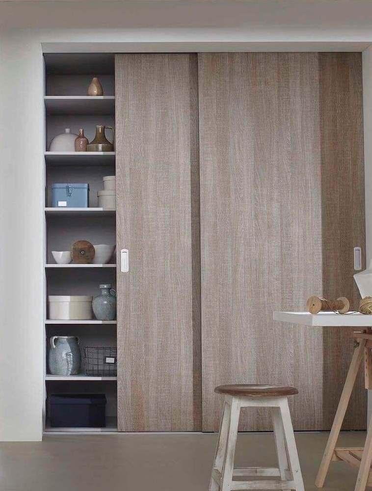 Holzschiebetür, welche ein Regal mit Geschirr verdeckt
